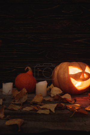 Photo pour Carved spooky Halloween pumpkin, autumnal leaves and candles on wooden rustic table - image libre de droit