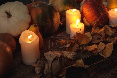 Photo pour Dry foliage, burning candles, ripe pumpkin on wooden rustic table - image libre de droit