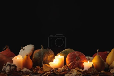 Photo for Dry foliage, burning candles, ripe pumpkin on wooden rustic table isolated on black - Royalty Free Image