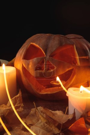 Photo for Dry foliage, burning candles and Halloween carved pumpkin on wooden rustic table isolated on black - Royalty Free Image
