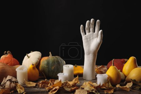 Photo for Dry foliage, candles, ripe pumpkins and decorative hand on wooden rustic table isolated on black - Royalty Free Image