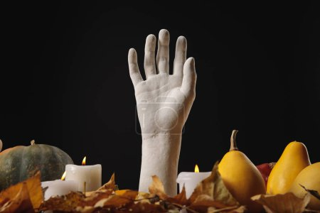 Photo for Dry foliage, burning candles, ripe pumpkins and decorative hand on wooden rustic table isolated on black - Royalty Free Image