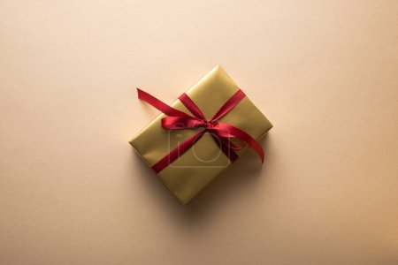 Photo pour Top view of golden gift box with red ribbon on beige background - image libre de droit
