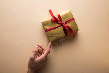 Foto de Cropped view of man touching golden gift box with red ribbon on beige background - Imagen libre de derechos