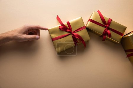 cropped view of man touching golden gift boxes with red ribbons on beige background