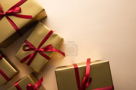 Photo pour Top view of golden gift boxes with red ribbons and bows on beige background - image libre de droit