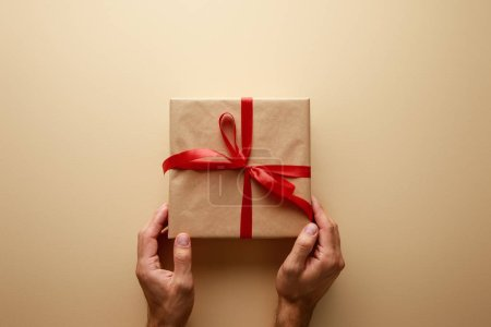 cropped view of man holding gift box in craft paper with red ribbon on beige background