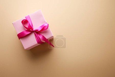 Foto de Top view of pink gift box with ribbon on beige background - Imagen libre de derechos