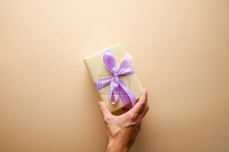 cropped view of man holding gift box with violet ribbon on beige background