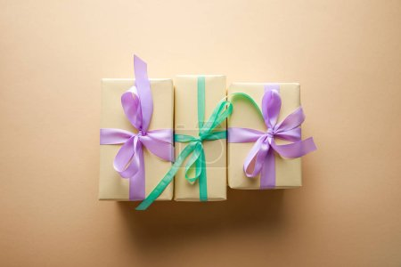 Photo pour Top view of gift boxes with violet and green ribbons on beige background - image libre de droit
