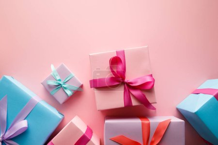 Photo pour Top view of colorful gift boxes with satin ribbons on pink background - image libre de droit
