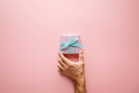 cropped view of man holding violet small gift box with blue satin ribbon on pink background