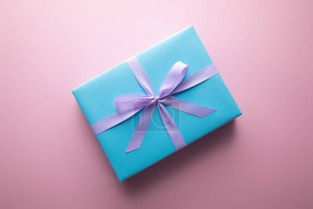 Foto de Top view of blue gift box with violet satin ribbon on pink background - Imagen libre de derechos
