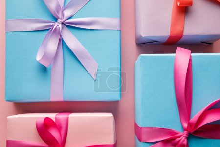 Photo pour Top view of colorful gift boxes with ribbons on pink background - image libre de droit
