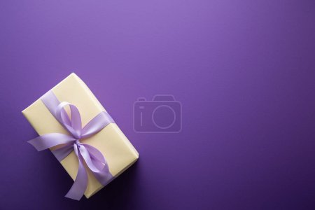 Photo for Top view of gift box with violet ribbon on purple background with copy space - Royalty Free Image