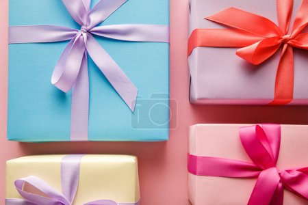 Foto de Top view of colorful gift boxes with ribbons on pink background - Imagen libre de derechos