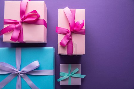 Photo for Top view of colorful gift boxes with ribbons and bows on purple background with copy space - Royalty Free Image