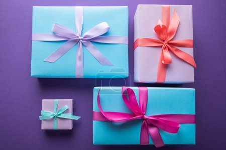 Photo pour Top view of colorful gift boxes with ribbons and bows on purple background - image libre de droit