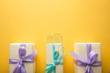 Photo pour Pose plate avec des boîtes-cadeaux avec des rubans violets et bleus sur fond jaune avec espace de copie - image libre de droit