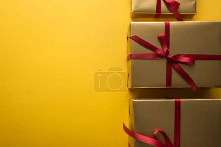 Photo pour Top view of golden gift boxes with red ribbons on yellow background with copy space - image libre de droit
