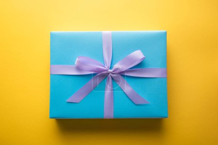 Photo for Top view of blue gift box with violet ribbon on yellow background - Royalty Free Image