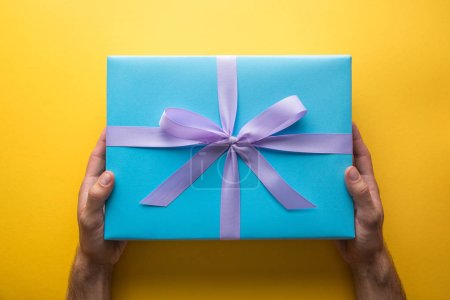 cropped view of man holding blue gift box with violet ribbon on yellow background