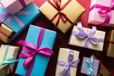 Photo pour En haut des boîtes-cadeaux colorées avec des rubans sur fond rouge - image libre de droit