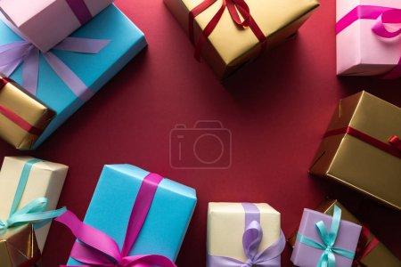 Photo pour En haut des boîtes-cadeaux colorées avec rubans sur fond rouge avec espace pour la photocopie - image libre de droit