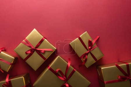 Photo for Top view of golden gift boxes with ribbons on red background - Royalty Free Image