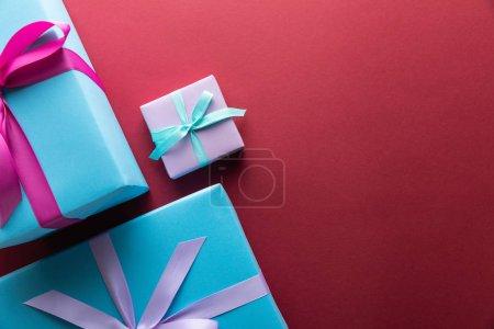 Photo pour Vue du haut des boîtes à cadeaux bleues et violettes avec rubans sur fond rouge avec espace pour la copie - image libre de droit