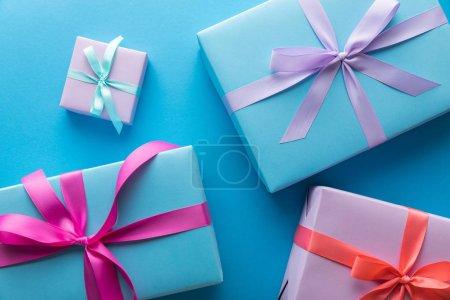 Photo pour En haut des boîtes-cadeaux colorées avec des rubans sur fond bleu - image libre de droit