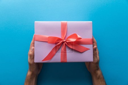cropped view of man holding violet gift box with red ribbon on blue background
