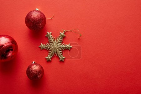 Foto de Top view of shiny Christmas baubles and golden snowflake on red background - Imagen libre de derechos