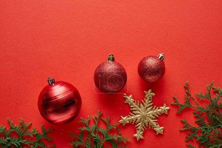 Foto de Top view of shiny Christmas baubles, fir branches and golden snowflake on red background - Imagen libre de derechos