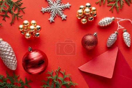 Foto de Top view of shiny Christmas decoration, envelope and thuja on red background - Imagen libre de derechos
