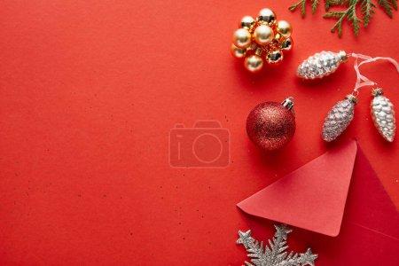 Photo pour Vue d'en haut de la brillante décoration de Noël, enveloppe et thuja sur fond rouge avec espace de photocopie - image libre de droit
