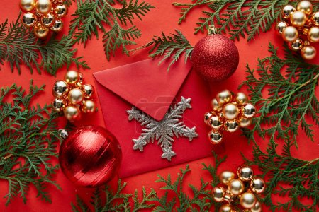 Foto de Top view of shiny Christmas decoration, envelope with snowflake and thuja on red background - Imagen libre de derechos
