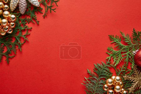 Photo for Top view of shiny Christmas decoration on green thuja branches on red background with copy space - Royalty Free Image