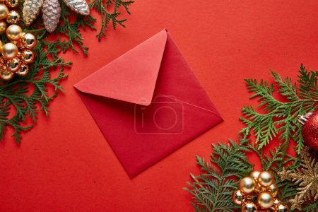 top view of red envelope near shiny Christmas decoration on green thuja branches on red background