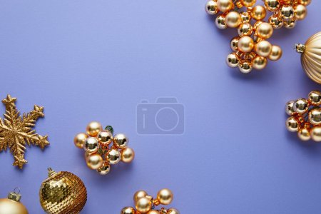 top view of shiny golden Christmas decoration on blue background with copy space