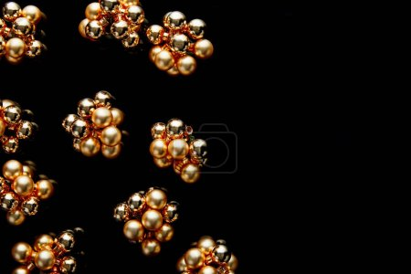 Foto de Top view of shiny golden Christmas decoration isolated on black with copy space - Imagen libre de derechos