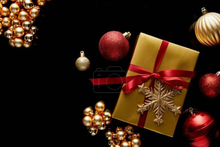 Foto de Top view of shiny golden Christmas gift with red ribbon and snowflake near baubles isolated on black - Imagen libre de derechos