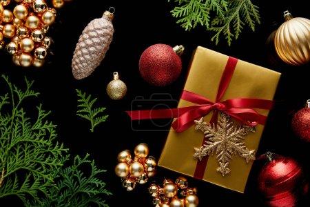 Photo pour Vue de dessus de la décoration de Noël dorée brillante, branches de thuja vert et boîte cadeau isolé sur noir - image libre de droit