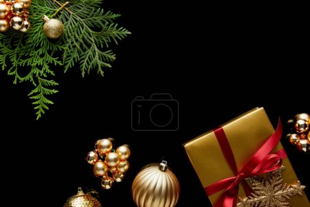 Photo for Top view of shiny golden Christmas decoration, green thuja branches and gift box isolated on black - Royalty Free Image