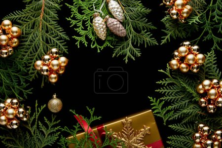 top view of shiny golden Christmas decoration, green thuja branches and gift box isolated on black with copy space