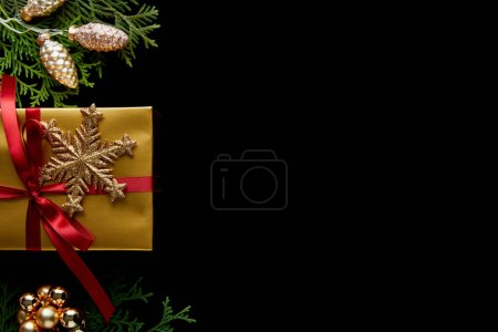Foto de Top view of shiny golden Christmas decoration, green thuja branches and gift isolated on black with copy space - Imagen libre de derechos