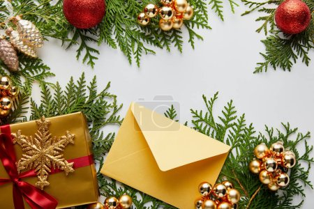 Photo for Top view of shiny golden Christmas decoration, gift and envelope on green thuja branches isolated on white - Royalty Free Image