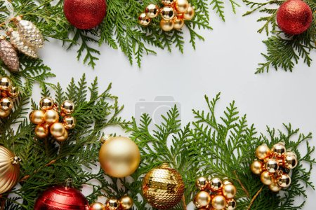 Photo for Top view of shiny golden and red Christmas decoration on green thuja branches isolated on white - Royalty Free Image