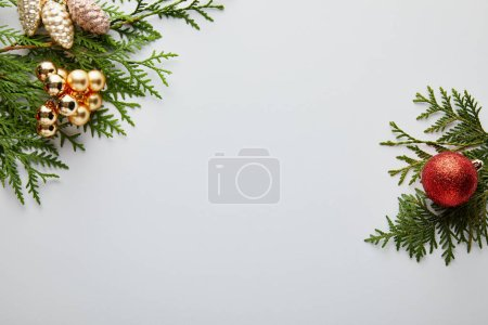 top view of shiny golden and red Christmas decoration on green thuja branches isolated on white with copy space