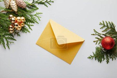 vue de dessus de la décoration de Noël dorée et rouge brillante sur les branches de thuja vert près de l'enveloppe isolée sur blanc